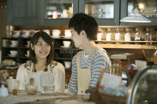 カウンターで微笑むカフェの店員の写真素材 [FYI04552625]