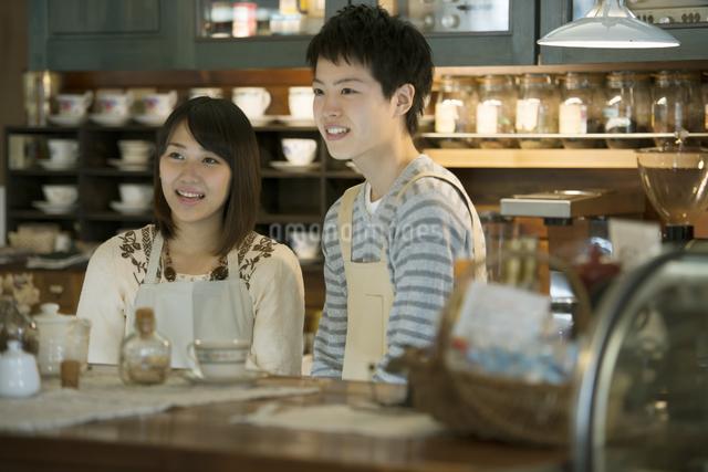 カウンターで微笑むカフェの店員の写真素材 [FYI04552626]