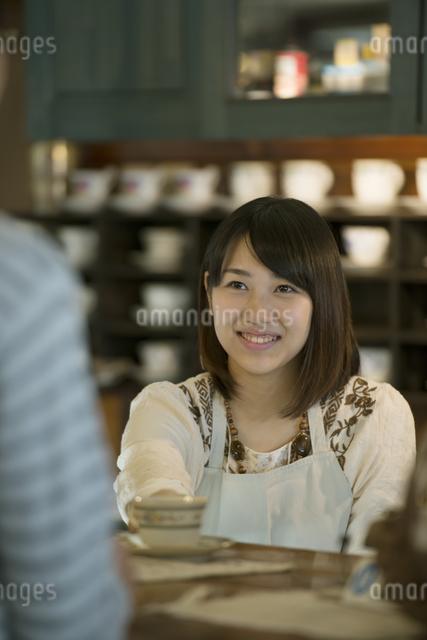 カウンターで微笑むカフェの店員の写真素材 [FYI04552627]