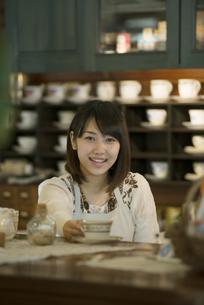 カウンターで微笑むカフェの店員の写真素材 [FYI04552628]