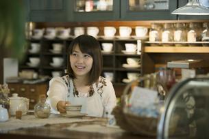 カウンターで微笑むカフェの店員の写真素材 [FYI04552629]