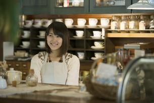 カウンターで微笑むカフェの店員の写真素材 [FYI04552630]