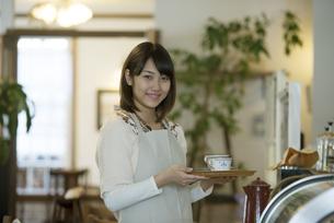 飲み物を運ぶカフェの店員の写真素材 [FYI04552631]