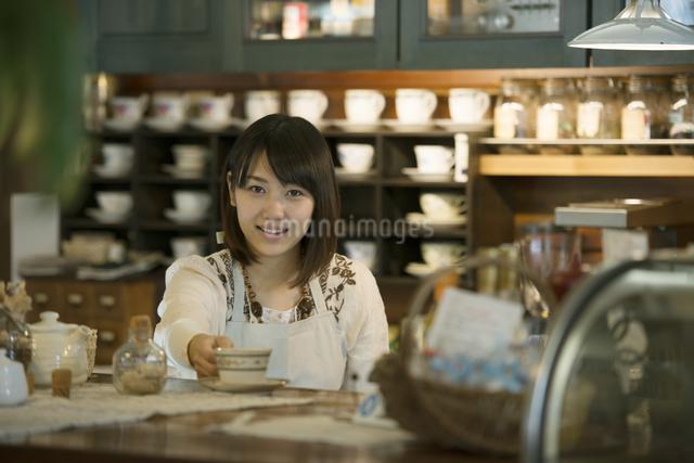 カウンターで微笑むカフェの店員の写真素材 [FYI04552632]