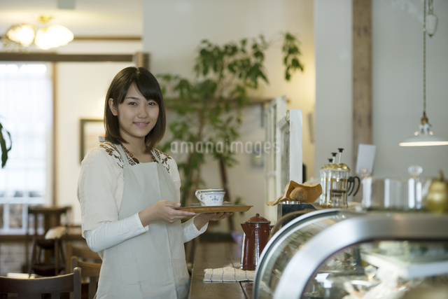 飲み物を運ぶカフェの店員の写真素材 [FYI04552633]