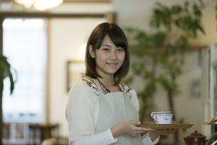 飲み物を運ぶカフェの店員の写真素材 [FYI04552634]