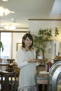 飲み物を運ぶカフェの店員の写真素材 [FYI04552635]