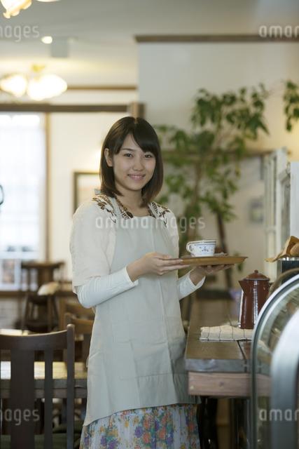 飲み物を運ぶカフェの店員の写真素材 [FYI04552636]