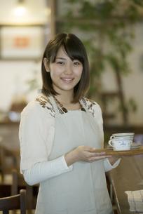 飲み物を運ぶカフェの店員の写真素材 [FYI04552637]