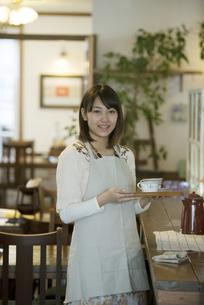 飲み物を運ぶカフェの店員の写真素材 [FYI04552638]