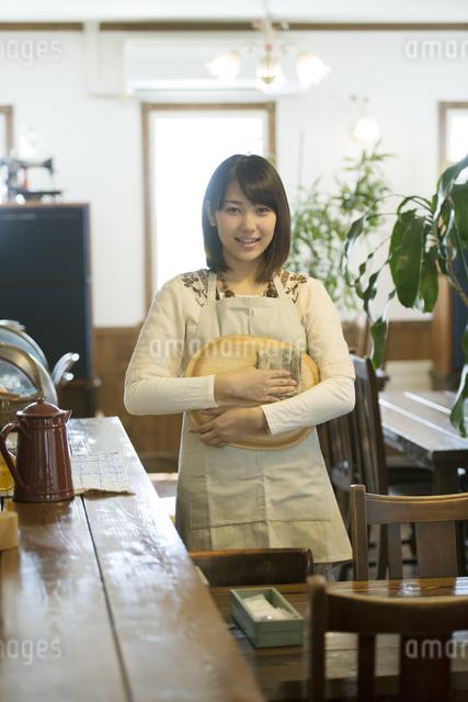 お盆を持ち微笑むカフェの店員の写真素材 [FYI04552639]