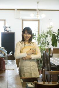 お盆を持ち微笑むカフェの店員の写真素材 [FYI04552640]