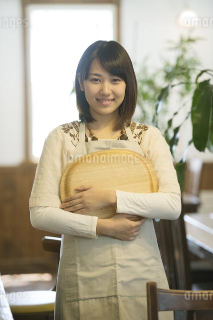 お盆を持ち微笑むカフェの店員の写真素材 [FYI04552642]