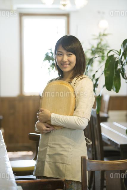 お盆を持ち微笑むカフェの店員の写真素材 [FYI04552644]