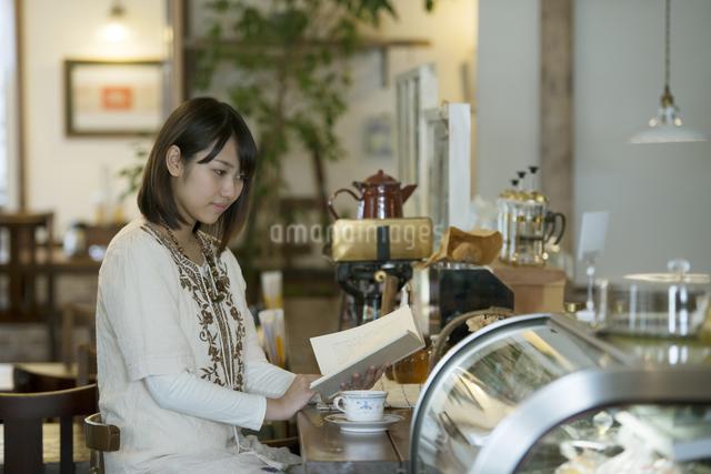 カフェで読書をする女性の写真素材 [FYI04552659]