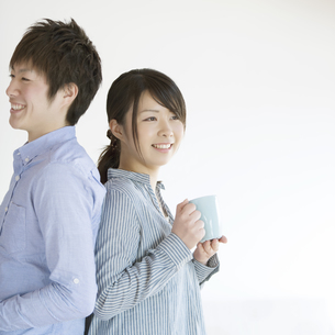 コーヒーカップを持ち微笑むカップルの写真素材 [FYI04552685]