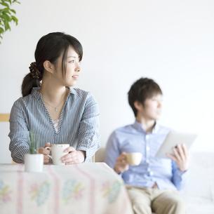 部屋でコーヒーを飲むカップルの写真素材 [FYI04552706]