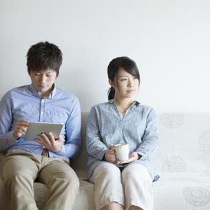ソファーに座りリラックスをするカップルの写真素材 [FYI04552711]