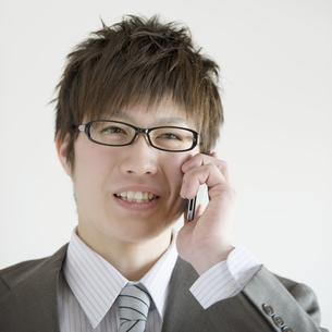 スマートフォンで電話をするビジネスマンの写真素材 [FYI04552724]