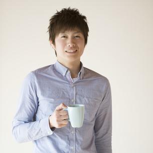 コーヒーカップを持ち微笑む男性の写真素材 [FYI04552740]