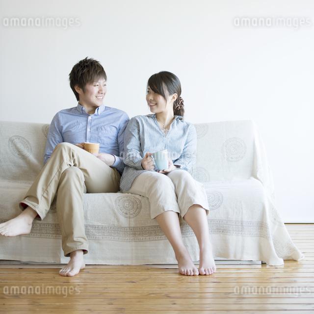 ソファに座り微笑むカップルの写真素材 [FYI04552760]