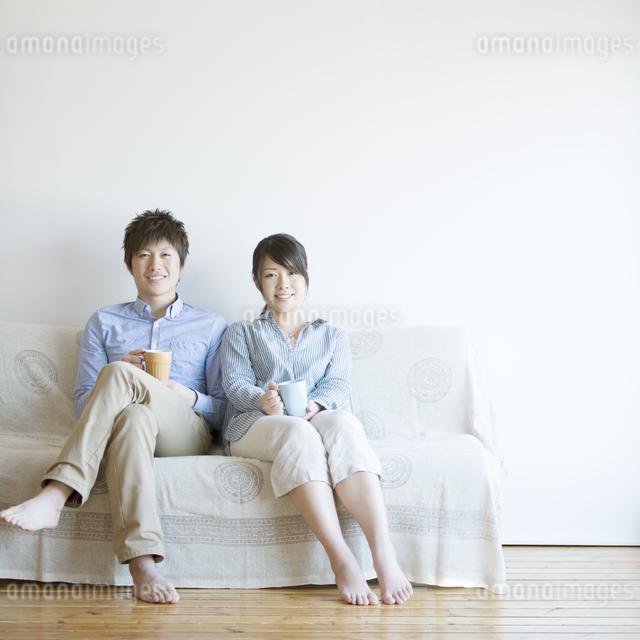 ソファに座り微笑むカップルの写真素材 [FYI04552764]