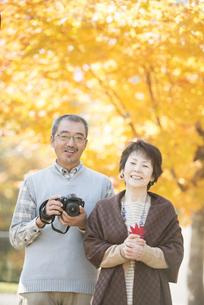紅葉の前で微笑むシニア夫婦の写真素材 [FYI04552784]