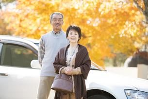 紅葉の前で微笑むシニア夫婦の写真素材 [FYI04552807]