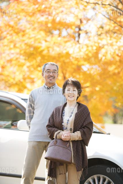 紅葉の前で微笑むシニア夫婦の写真素材 [FYI04552808]