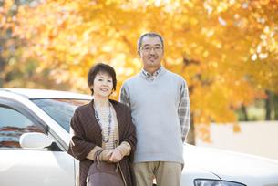 紅葉の前で微笑むシニア夫婦の写真素材 [FYI04552812]