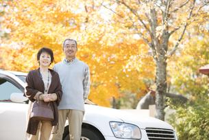 紅葉の前で微笑むシニア夫婦の写真素材 [FYI04552823]