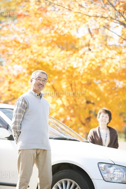 紅葉の前で微笑むシニア夫婦の写真素材 [FYI04552825]