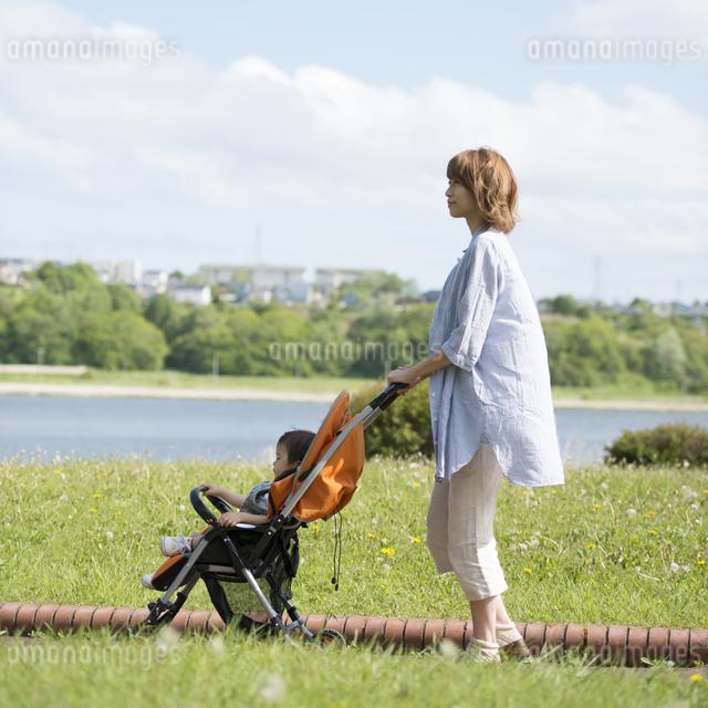 赤ちゃんの乗るベビーカーを押す母親の写真素材 [FYI04552934]