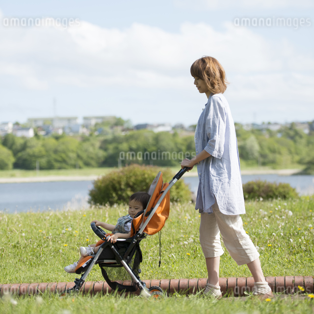 赤ちゃんの乗るベビーカーを押す母親の写真素材 [FYI04552936]