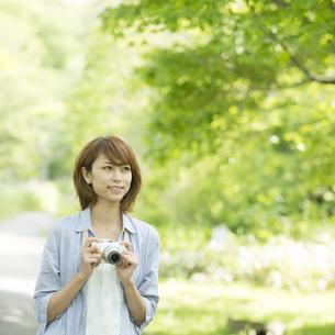 カメラを持ち微笑む女性の写真素材 [FYI04552937]