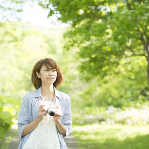 カメラを持ち微笑む女性の写真素材 [FYI04552941]