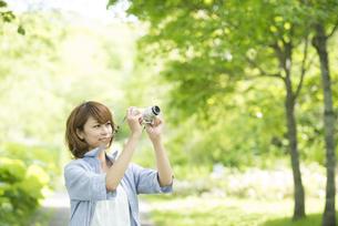 カメラを持ち微笑む女性の写真素材 [FYI04552945]