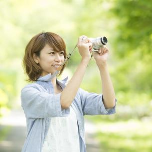カメラを持ち微笑む女性の写真素材 [FYI04552947]