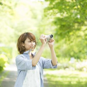 カメラを持ち微笑む女性の写真素材 [FYI04552948]