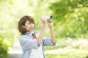 カメラを持ち微笑む女性の写真素材 [FYI04552949]