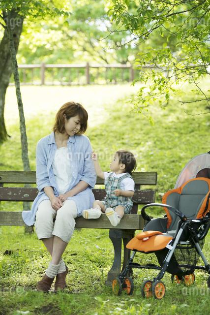 ベンチに座り微笑む親子の写真素材 [FYI04552955]