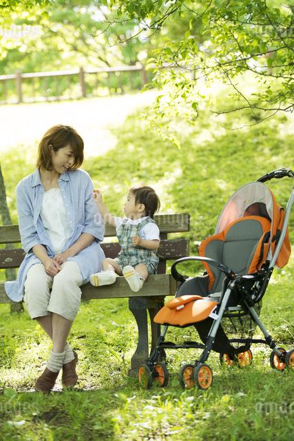 ベンチに座り微笑む親子の写真素材 [FYI04552957]