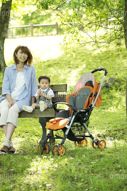 ベンチに座り微笑む親子の写真素材 [FYI04552959]