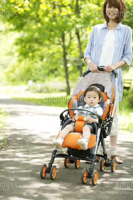 赤ちゃんの乗るベビーカーを押す母親の写真素材 [FYI04553004]