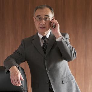 スマートフォンで電話をするビジネスマンの写真素材 [FYI04553022]