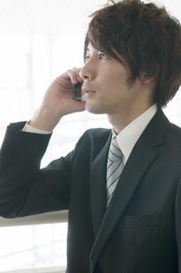 スマートフォンで電話をするビジネスマンの写真素材 [FYI04553040]