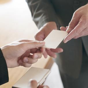 名刺交換をするビジネスマンの手元の写真素材 [FYI04553080]