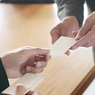 名刺交換をするビジネスマンの手元の写真素材 [FYI04553081]
