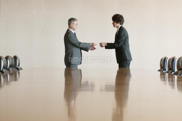 会議室で名刺交換をするビジネスマンの写真素材 [FYI04553093]