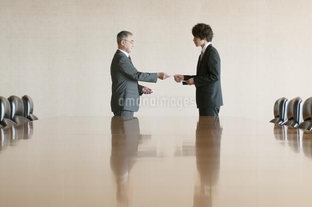 会議室で名刺交換をするビジネスマンの写真素材 [FYI04553095]